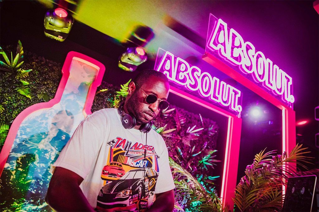 DJ spins records in front of neon Absolut signage. The festival activation spread a message of acceptance for all.