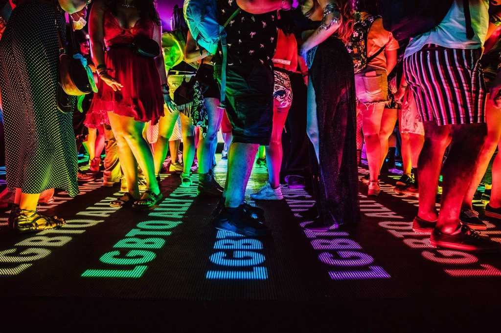 Event goers stand over a rainbow lit dance floor with LGBTQ Ally written in LEDs. The activation acted as an oasis in the desert.