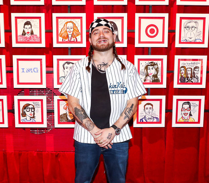 Napkin Killa smiles wide in front of his portraits of celebrities at Target's 2016 NYFW event.