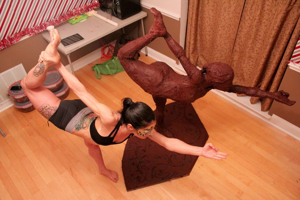 Yoga instructor and studio owner Kelly Senn poses in dancer's pose so The Chocolate Genius can create a sculpture live at Orlando Power Yoga's holiday party.