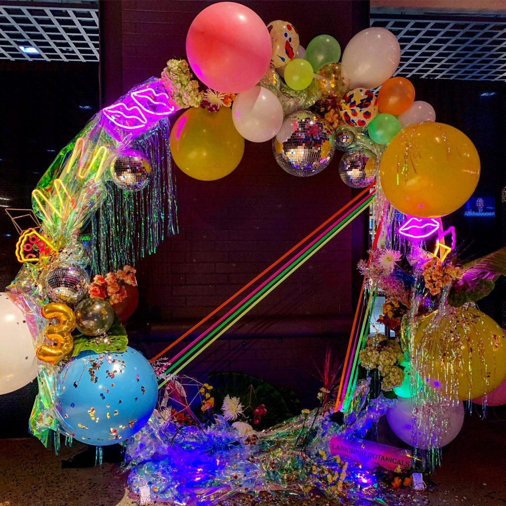 Reused tinsel and balloons by Larkspur Botanicals at the Midnight Market Neon Party.