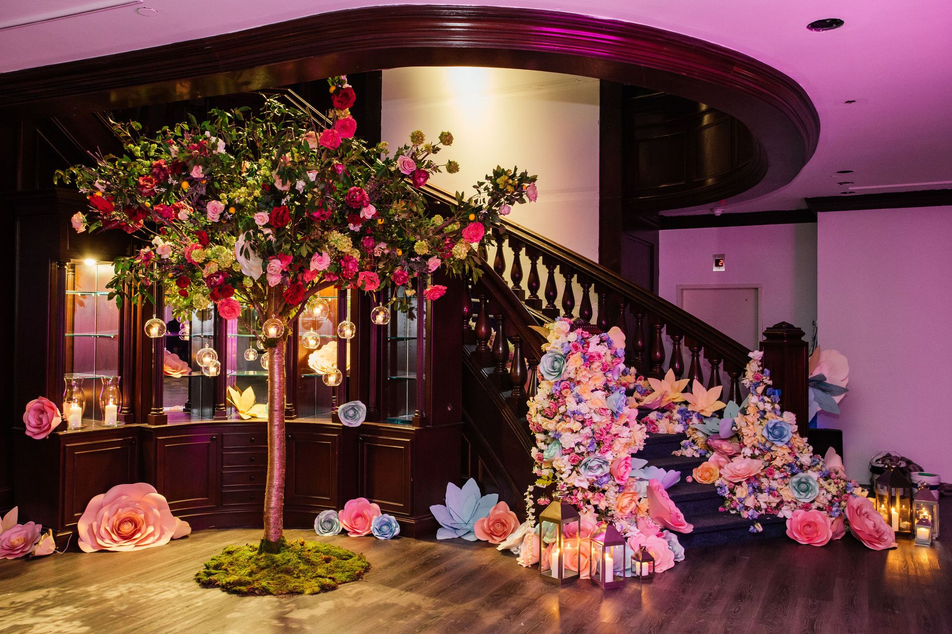 Staircase with decorative paper flowers next to a free standing tree with flowers and hanging ornaments