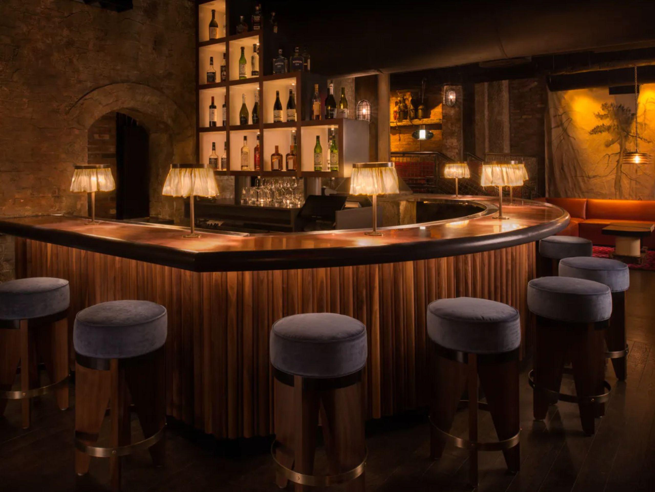 Curved sleek bar with blue velvet bar stools