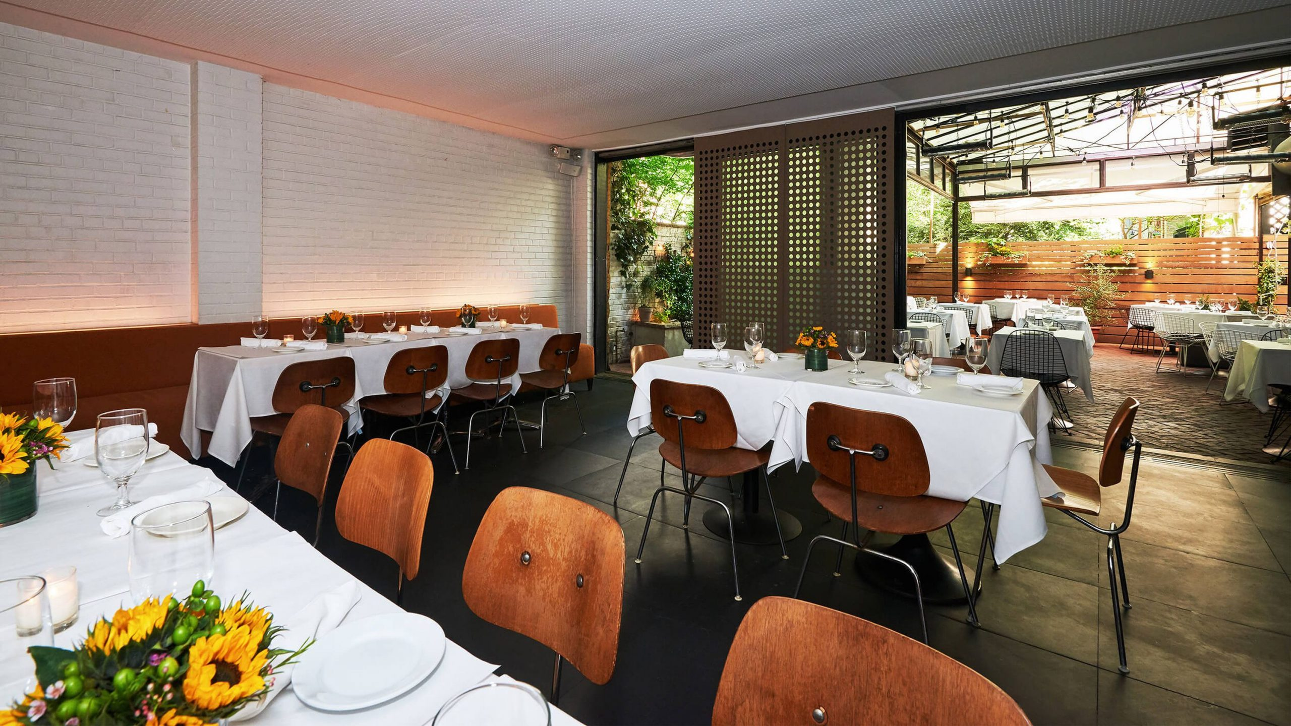 Covered outdoor dining area with multiple white linen tables