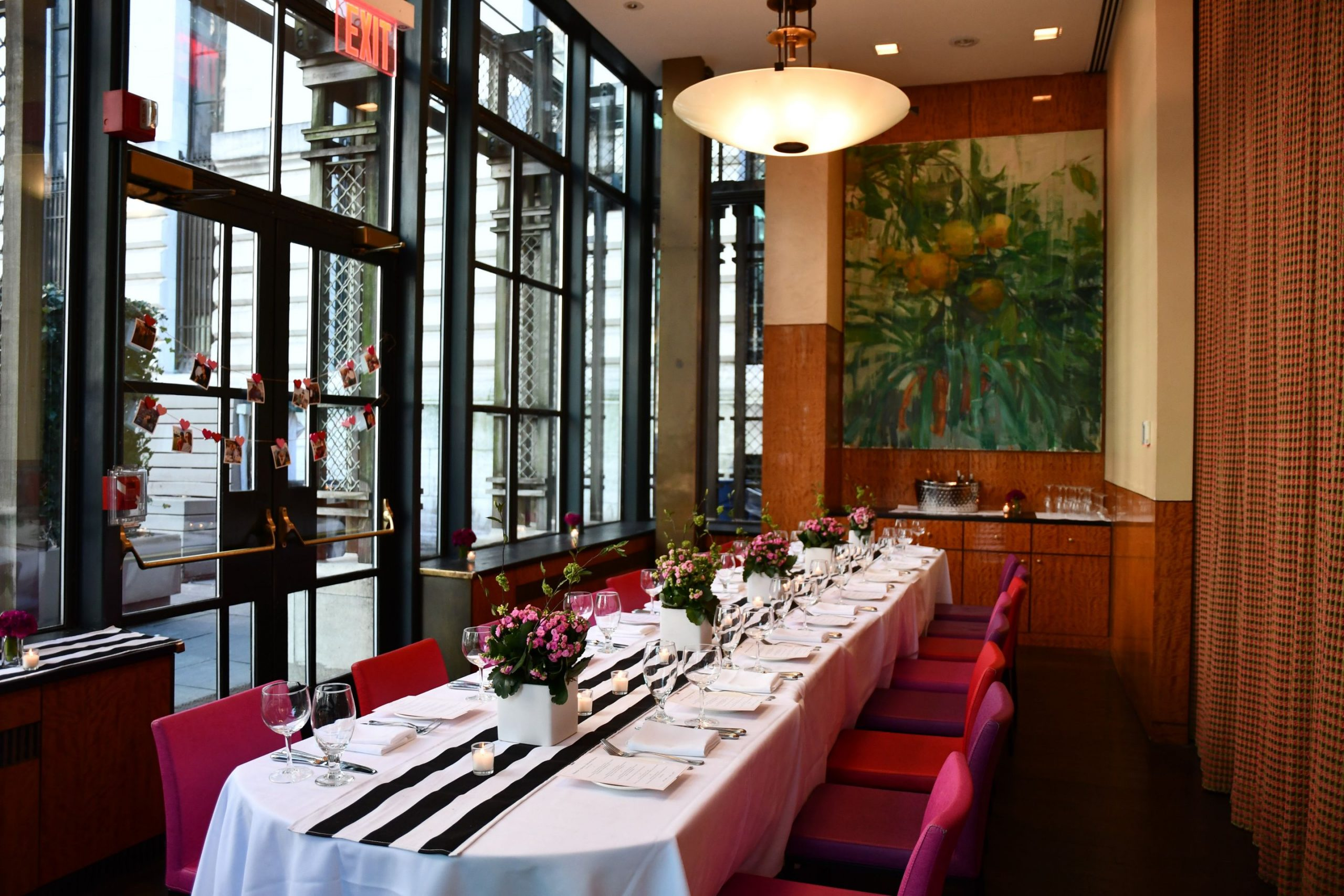 Long dining table with black and white runner with pink chairs and pink floral arrangements