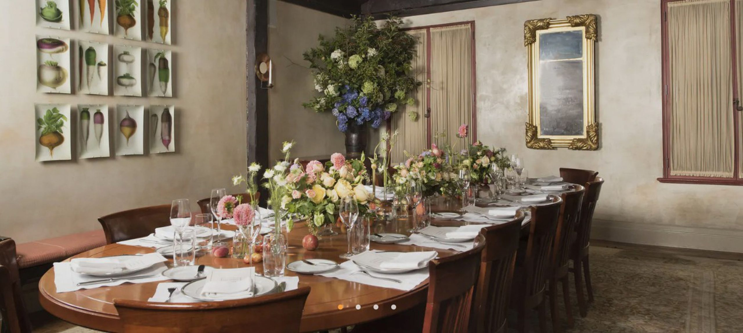 Long oval wooden dining table with set flatware and pastel flower arrangements