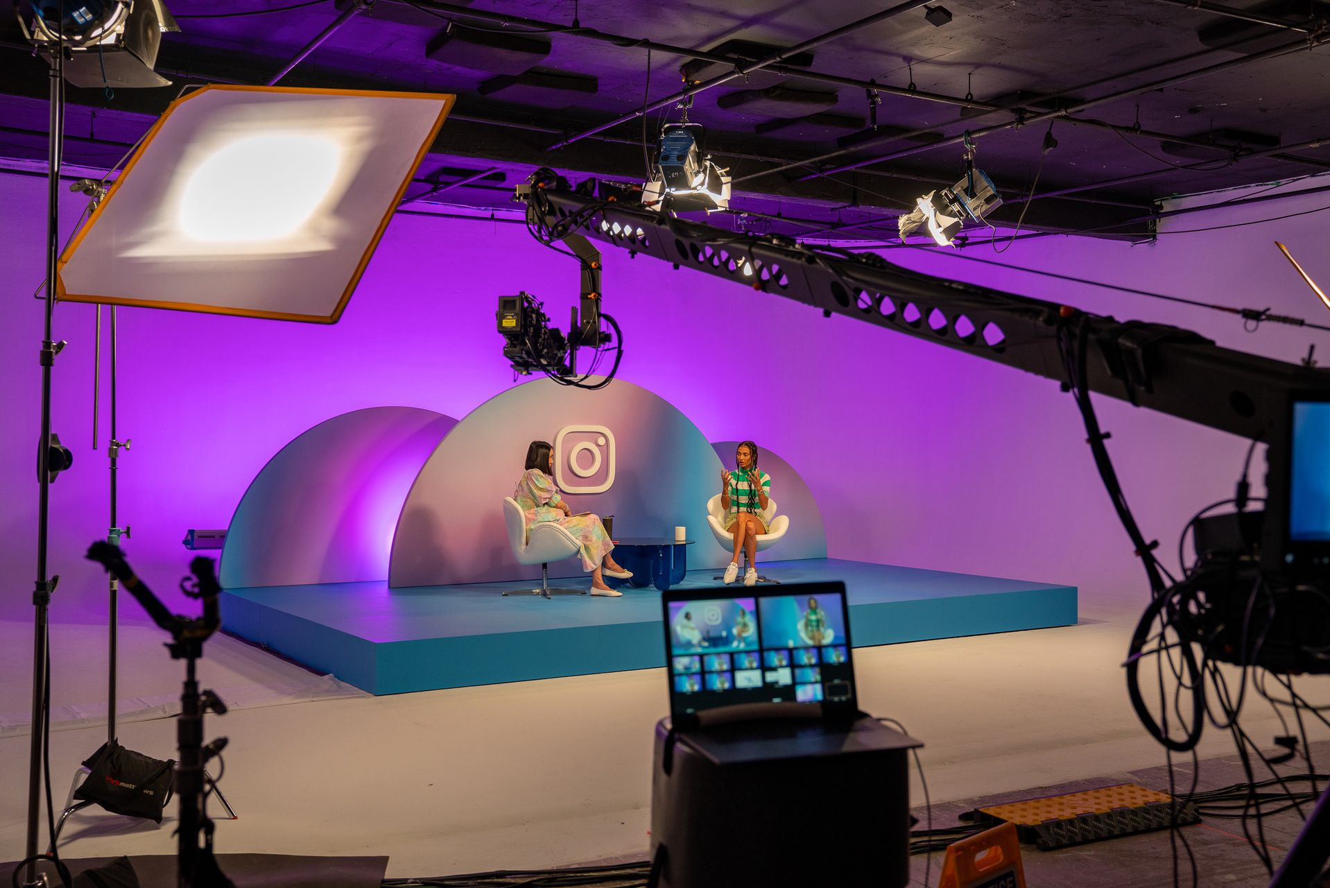 A stage with two women sitting being filmed by a camera