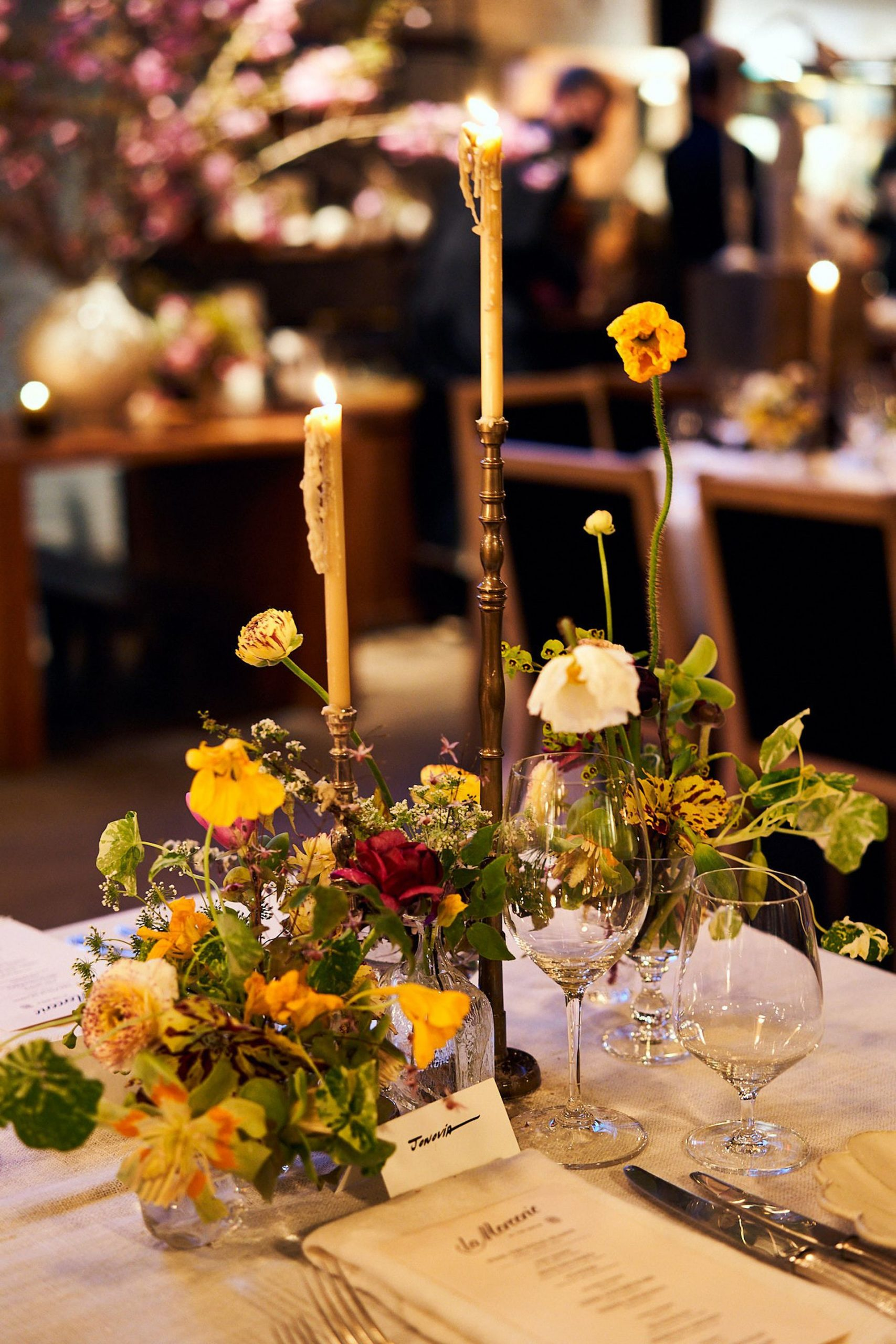 Wild baroque flower arrangement with tall lit candles on a white tablecloth table