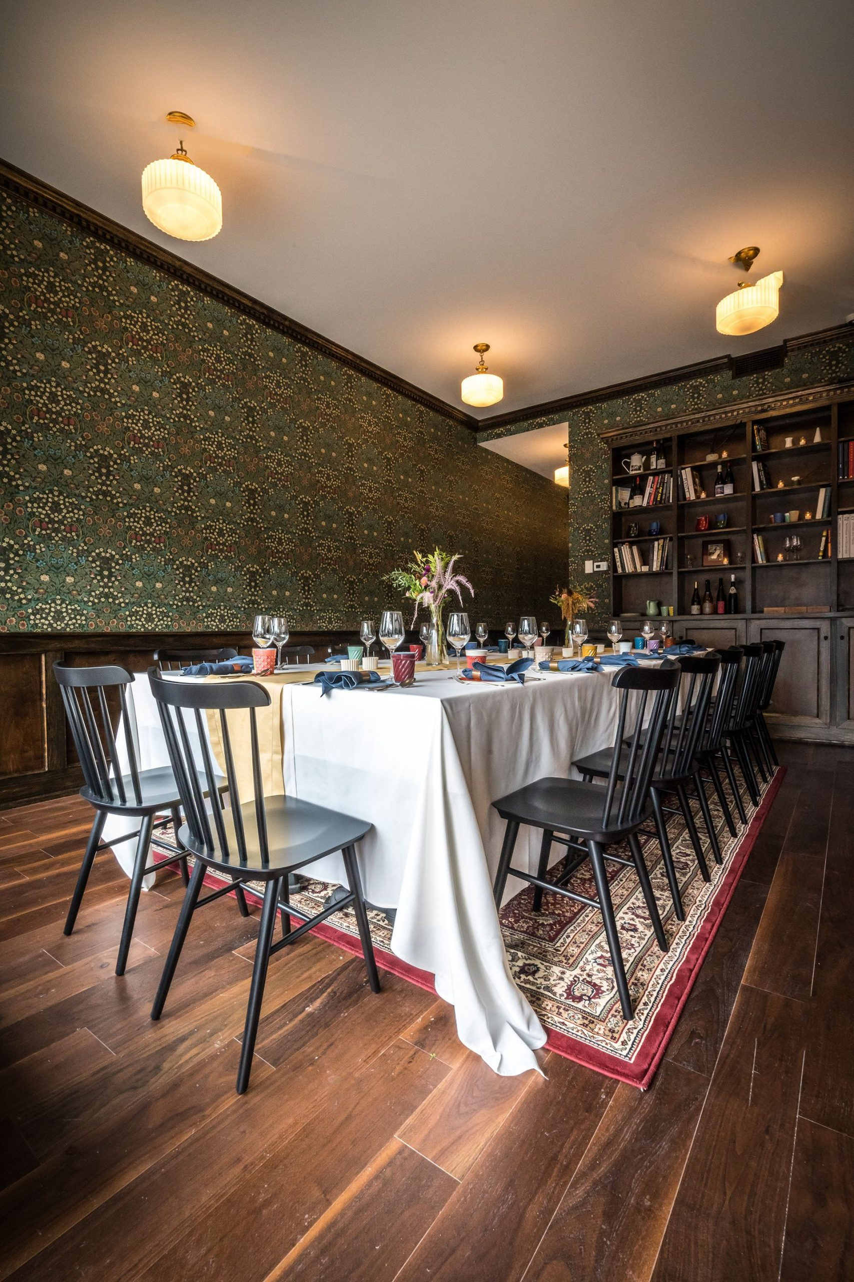 Long dining table with black chairs on oriental rug
