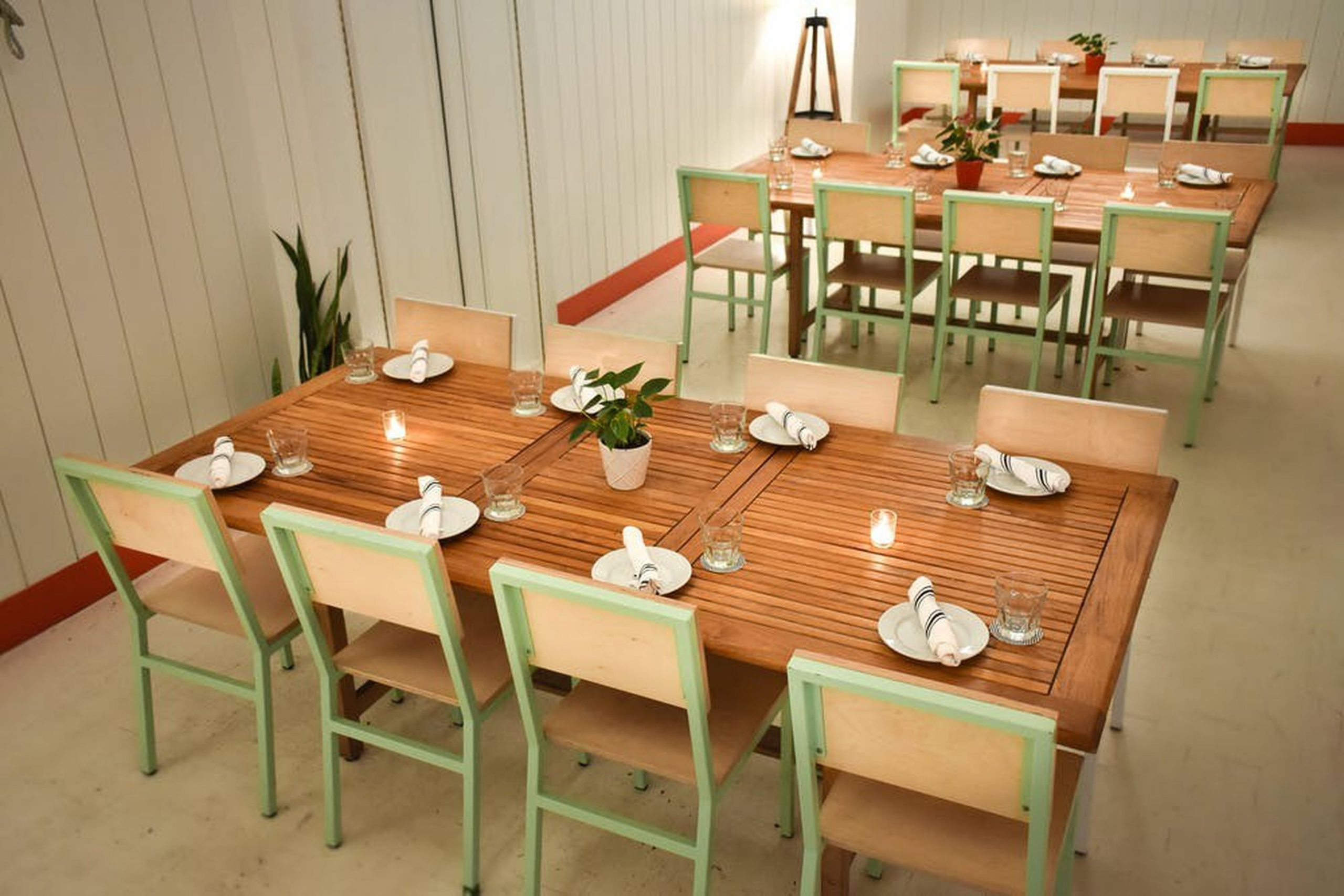 Three brown tables with green accented chairs in a minimalist space