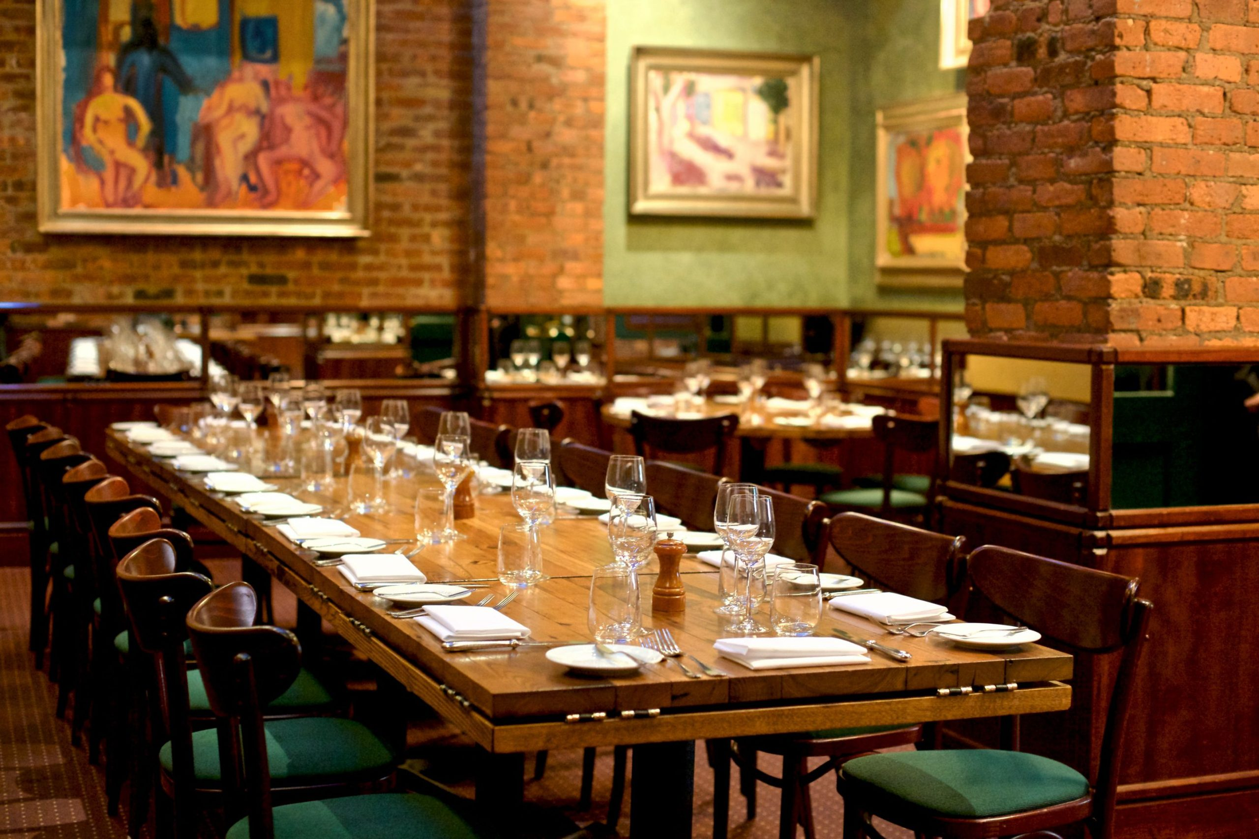 Long wooden table in a room with exposed brick walls and large paintings