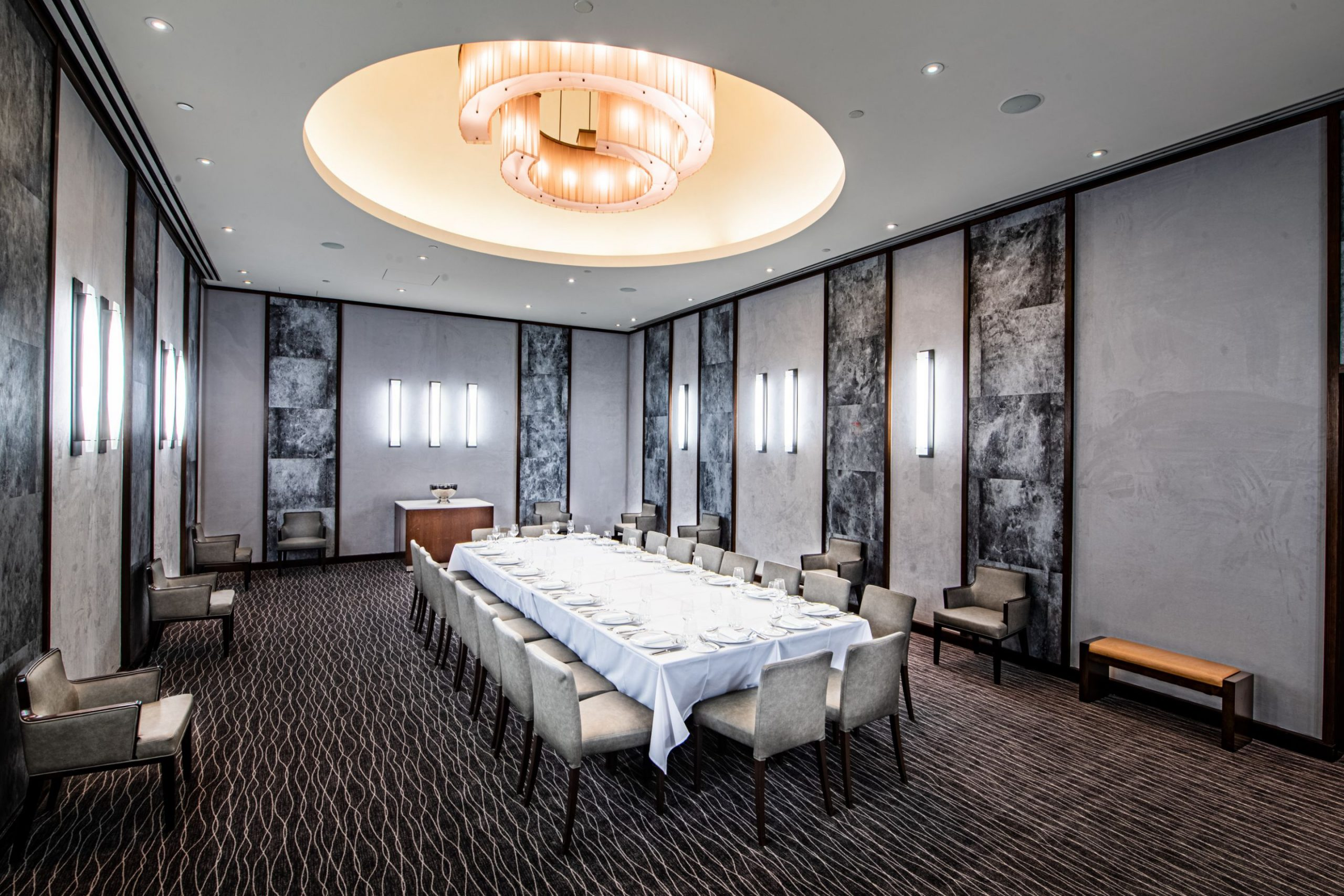 Large Dining room with concrete and marble walls and a long table with white tablecltoh
